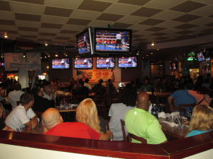 People watching TV at a restuarant. Restaurants are one industry who commonly use Surveillance and AV systems.