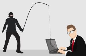 Man with fishing poll over computer dramatizing phishing, a common cybersecurity issue
