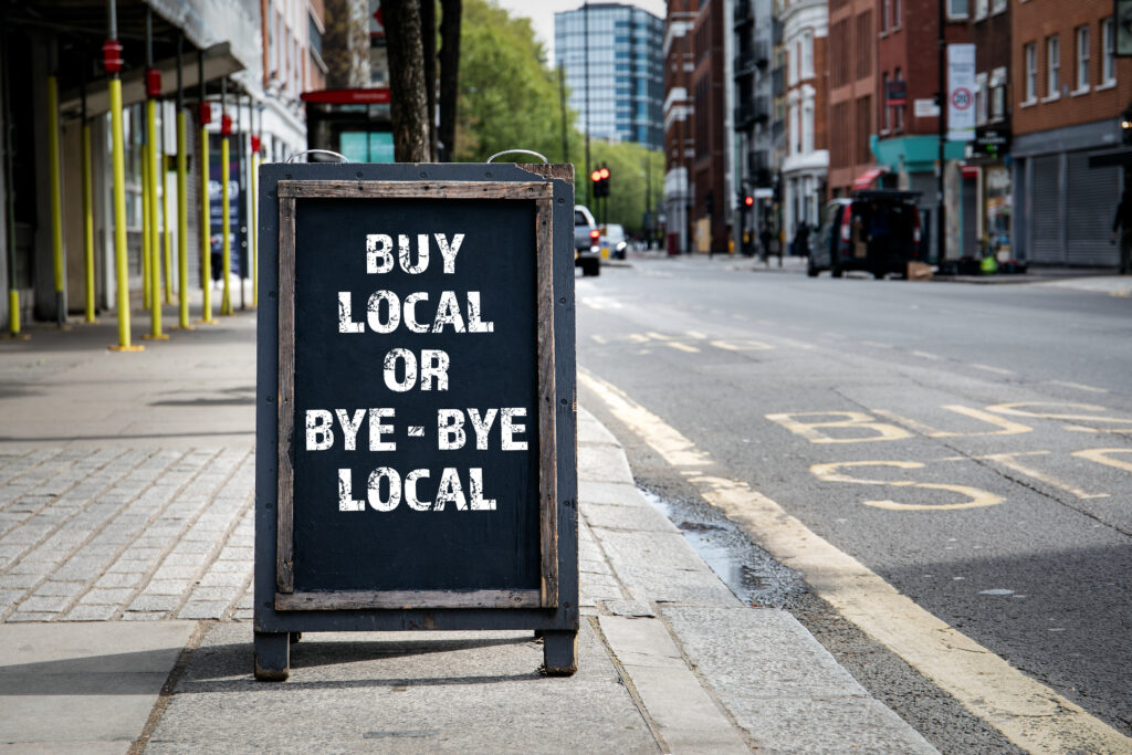 """Sign reading """"Buy Local or Bye-Bye Local"""" outside of a downtown shop."""